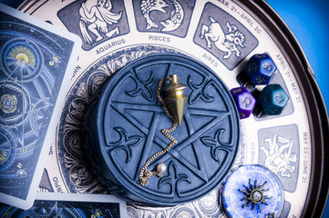 horoscope with zodiac signs, astrology dice, pendulum, pentagram and cars like esoteric concept