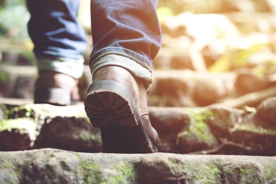 traveler tourist Close up leg of young hipster man one person hiker shoe boots hiking. tourist hikers in adventure forest step trail walking stepping going up the stairs with sunshine. travel concept.
