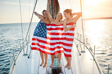 Sexy girls on the yacht in American flag Summer lifestyle.