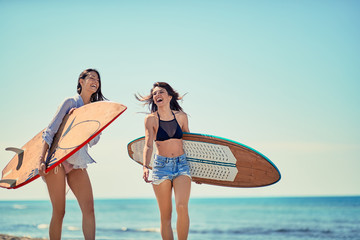 Young girls with a surf board on the beach Vacation. Extreme Sport.