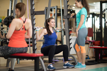 Pretty young women using barbell in gym. Trainer keep watch over her
