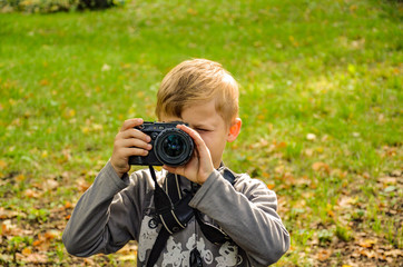 The boy is a photographer in the park.