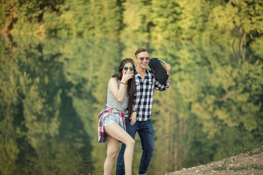 laughing couple in sunglasses listening to the music while strolling in the forest. side view photo