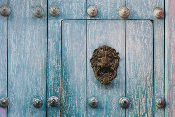 Door knocker in the form of an lion head on an old turquoise wooden door - Cartagena / Colombia