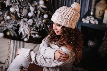 Pretty young woman in a room with christmas decoration. Winter mood, cozy home, scandinavian style
