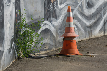 Stack of bright orange and white traffic cones next to painted concrete wall and green bush