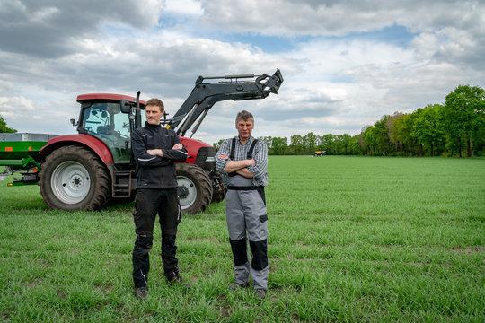 Ackerbau - Landwirt mit Sohn vor einem Traktor im Getreidebestand