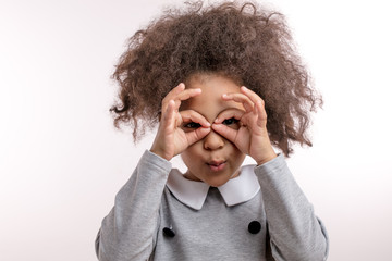 joyful kid with funny hair is looking through the fake glasses. have fun. entertainment concept