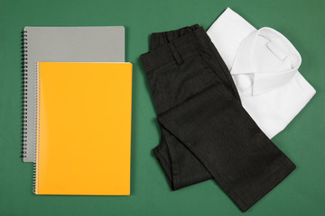 School uniform for boy and notebooks on color background, top view
