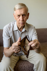 Sad old man holding an empty wallet.