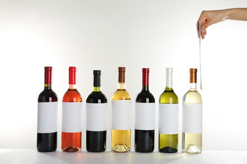 Bottles with different wine on white background