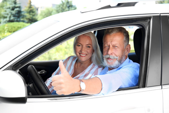 Happy senior couple travelling together in car