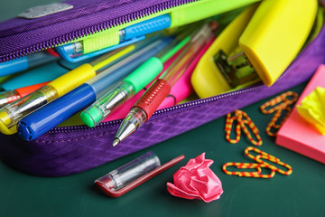 Different colorful stationery on chalkboard surface. Back to school