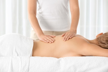 Relaxed woman receiving back massage in wellness center