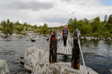 Girl with backpack crossing river in Femundsmarka national park, Norway