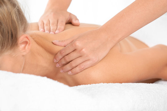 Relaxed woman receiving shoulders massage in wellness center