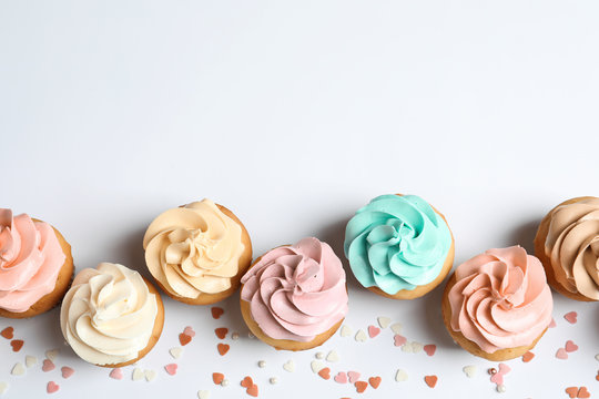 Flat lay composition with delicious birthday cupcakes and space for text on white background