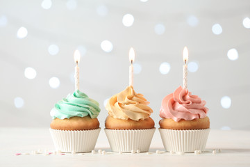 Delicious birthday cupcakes with burning candles on blurred lights background