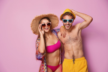 Happy young couple in beachwear on color background