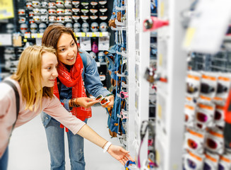 Two young happy women friends choose to buy modern anti ultraviolet goggles sunglasses in a sports shop with hiking equipment