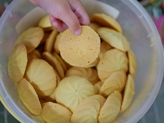 Close up and selective focus of baby's hand picking a piece of vanilla cookies from a bucket