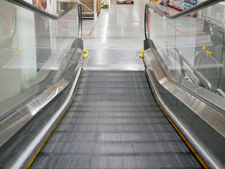 Close up of a moving shopping trolley escalator's steps that is about to collapse on each other, creating a flat platform to make it easier to get on and off the escalator