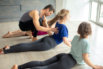 fitness, activity and healthy lifestyle concept - group of people with Yoga Trainer doing yoga pose in gym or studio