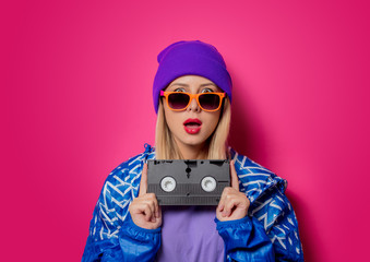 Young blonde girl in 90s sports jacket and VHS cassette on pink background.