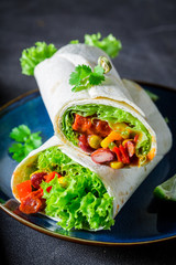 Burrito made of lettuce and vegetables with red salsa