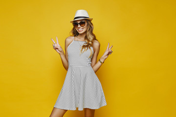 Beautiful and fashionable blonde model girl with sexy body and with charming smile, in white striped dress, in stylish hat and in trendy sunglasses posing at yellow background Wall mural