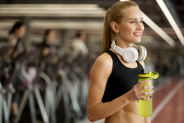 Young blond athletic woman wearing black closes holding water bottle in gym