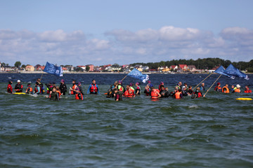 People march through the shallow seawater as they attend the traditional Herring March in Puck Bay