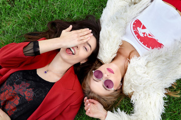 Two fashion young happy girl laying on green grass .Laughing and show tongue the other in pink sunglases.Stylish woman in red jacket and other in white fur and t-shirt.Fashion.World in pink glasses