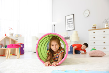 Cute little child in playing tunnel on floor, indoors