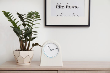 Modern clock on chest of drawers against light background