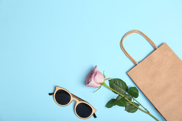 Stylish flat lay composition with shopping bag on color background