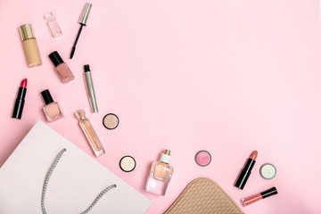 Flat lay composition with shopping bag and cosmetics on color background