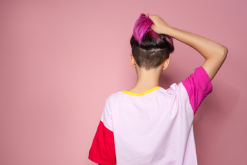 Young woman with trendy haircut against color background