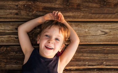 Portrait of a little red-haired girl, lying on wooden floor with copy space. Smiling four-years-old girl with beautiful blue eyes. Concept - happy childhood.