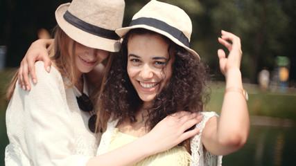 Beautiful young mixed race girls talking near lake and enjoying vacation.