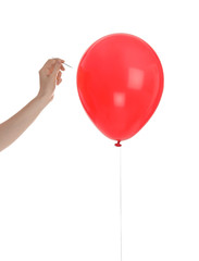 Woman piercing red balloon on white background