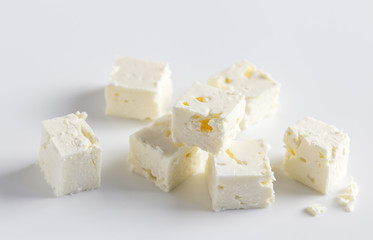 Feta cheese cubes on white background with space for text