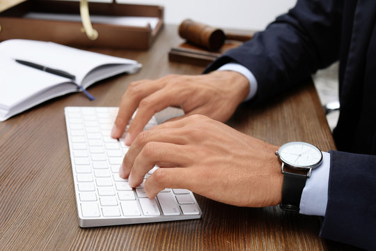 Male lawyer working with computer at table, closeup