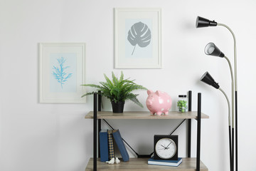 Shelving unit with decorative interior elements and piggy bank near white wall