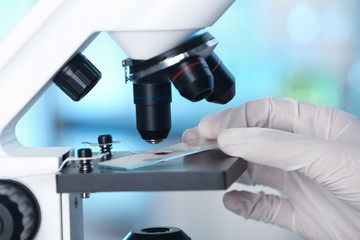 Analyst doing laboratory test with microscope, closeup. Chemical analysis