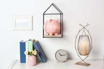 Cute piggy bank on shelf indoors. Stylish interior element