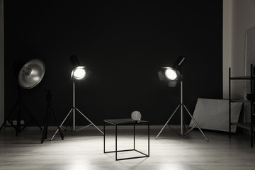 Interior of modern photo studio with table, clock and professional equipment