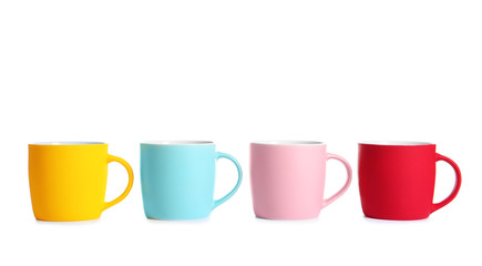 Different colorful cups on white background