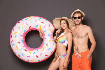 Young couple in beachwear with inflatable ring on dark background