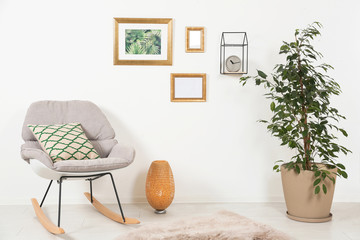 Stylish living room interior with ficus and rocking chair near white wall